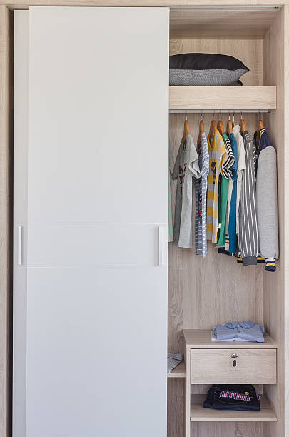 kid's clothes hanging in white wardrobe stock photo