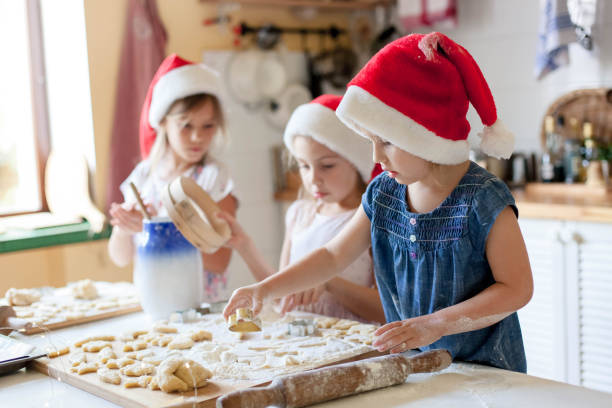 Kids cooking Christmas gingerbread cookies in cozy home kitchen. Funny children chefs stock photo