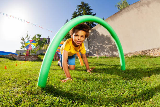 Kids crawl under course of barriers on his fours stock photo
