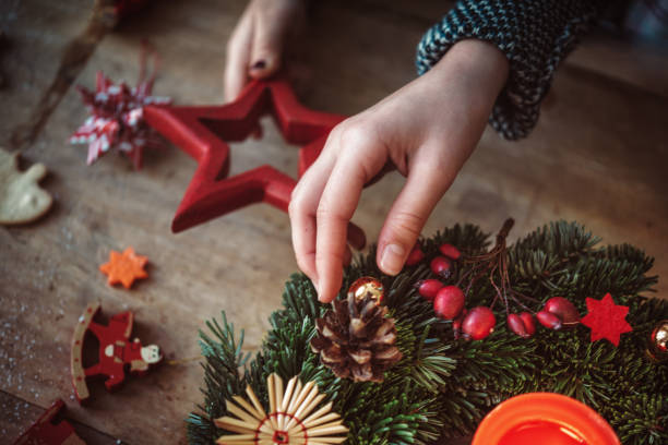 niños decorar la corona de adviento - adviento fotografías e imágenes de stock