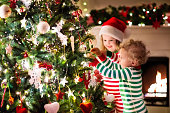 Kids decorating Christmas tree in beautiful living room