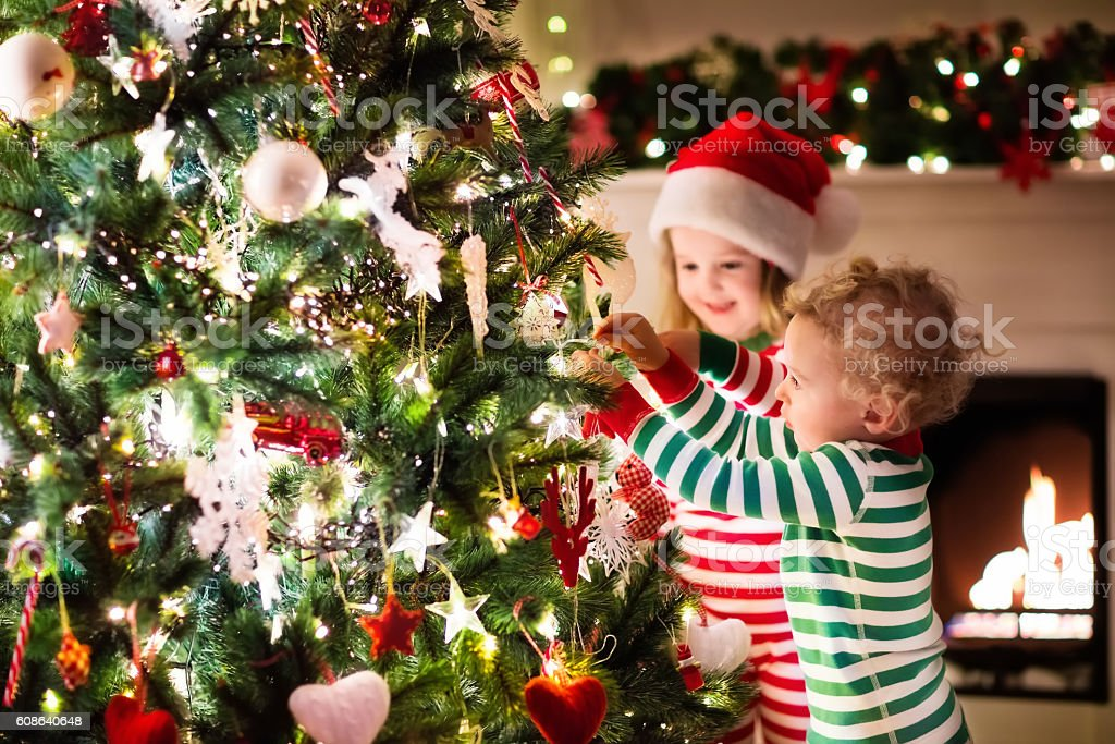Kids decorating Christmas tree in beautiful living room stock photo
