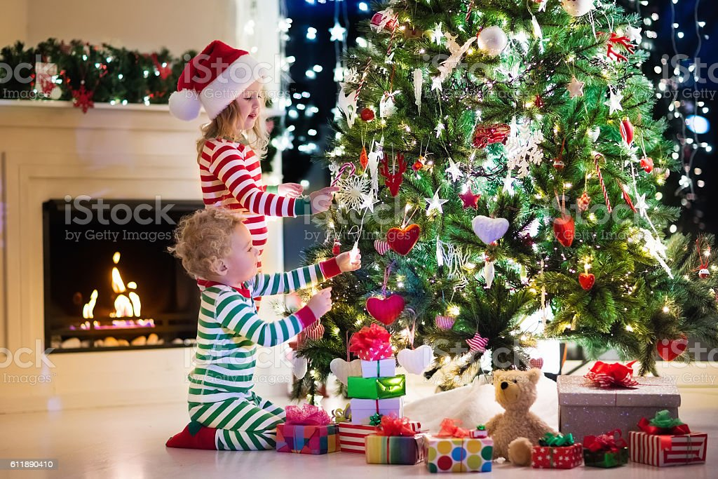 Kids Decorating Christmas Tree In Living Room With Fire