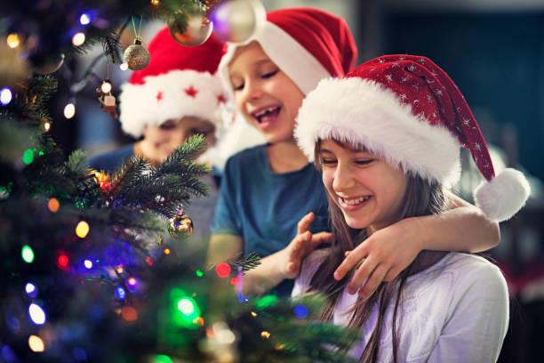 kinder schmücken weihnachtsbaum - weihnachten 7 jährige stock-fotos und bilder