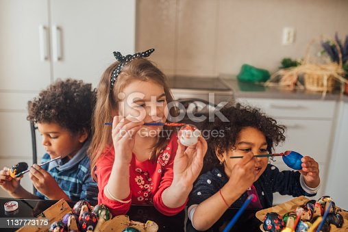 Happy young children coloring eggs for Easter celebration