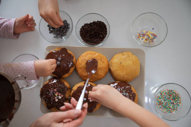 Kids decorating home made doughnuts with sprinkles stock photo