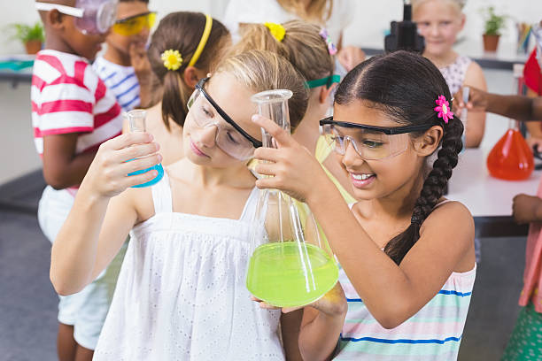 Kids doing a chemical experiment in laboratory stock photo