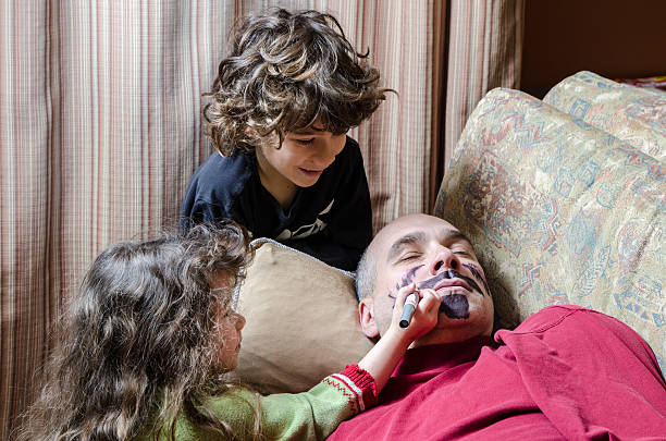 Kids drawing a mustache on father's face April fools day Two kids (boy and girl) are having fun drawing a moustache and a beard on their father's face while he his sleeping on the couch, april fools day stock pictures, royalty-free photos & images