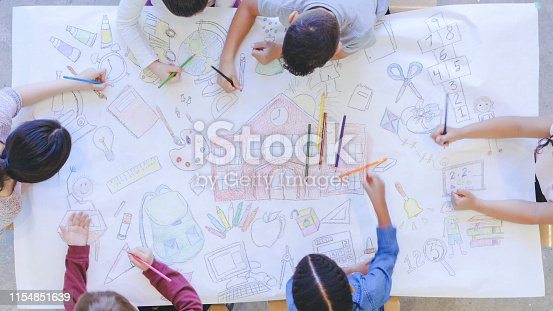 Aerial overhead view of multi-ethnic group of elementary age children coloring. The kids are seated around a table. They are creating a mural with colored pencils on paper. The children have colored a school and various school supplies.