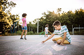 Multi-ethnic group of kids drawing with chalk on asphalt, on playground on day