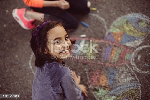 istock Kids drawing with chalk on asphalt 542109354
