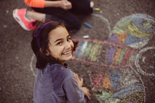 kids drawing with chalk on asphalt - chalk drawing stock photos and pictures