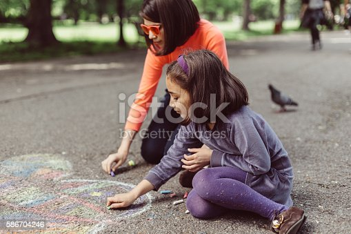 istock Kids drawing with chalk on asphalt 586704246