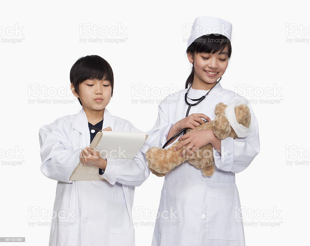 Kids dressed up as doctors checking teddy bear's vital signs stock photo
