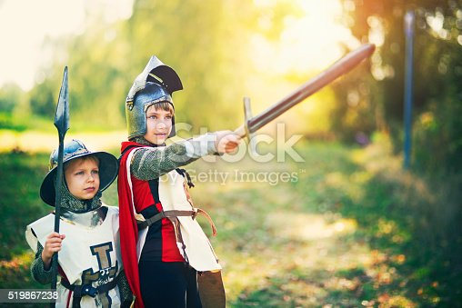 istock Kids dressed up as knights playing outdoors 519867238