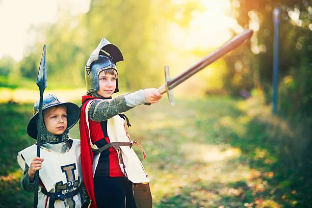 kinder verkleidet als ritter spielen im freien - mittelalterliche ritter stock-fotos und bilder