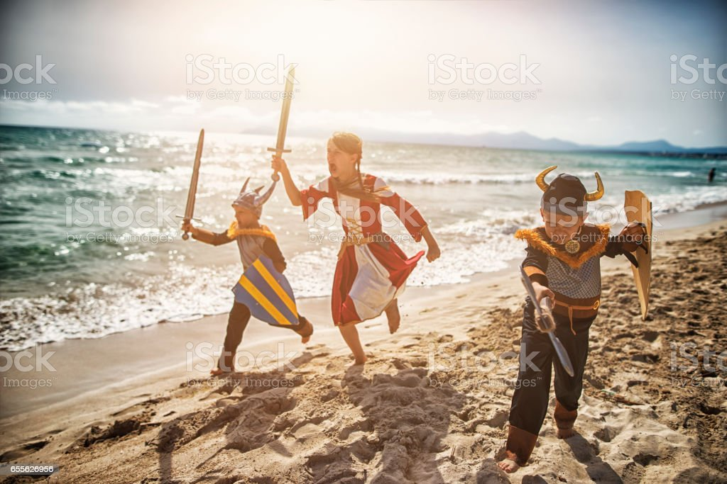 Kids dressed up as vikings charging thrrough the beach stock photo