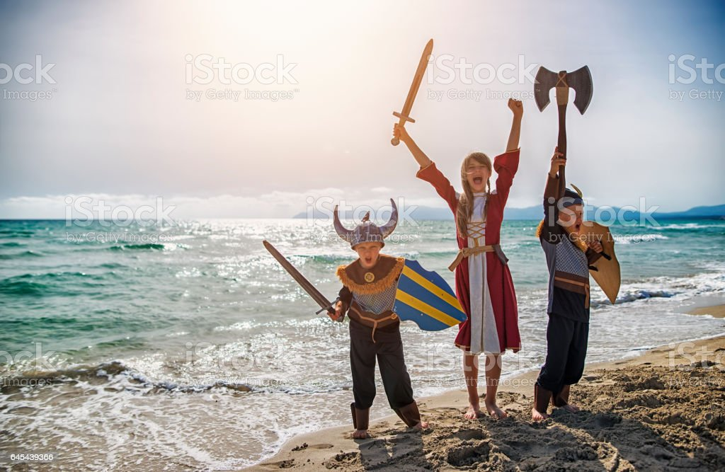 Kids dressed up as vikings playing on the beach stock photo
