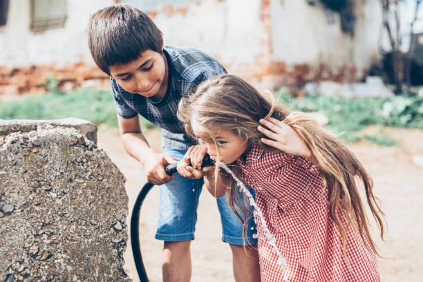 kids drinking water from a hose-pipe - boca suja imagens e fotografias de stock