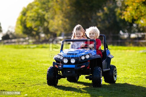 915609494istockphoto Kids driving electric toy car. Outdoor toys. 1126501896