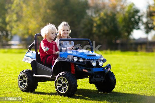 915609494istockphoto Kids driving electric toy car. Outdoor toys. 1126503101