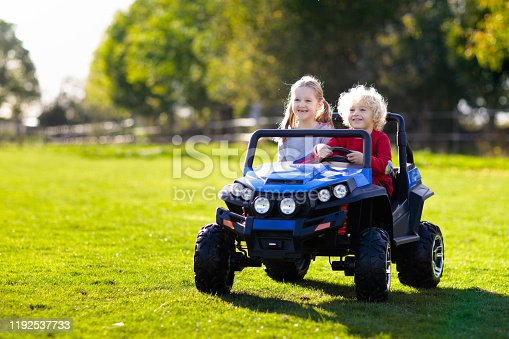 915609494 istock photo Kids driving electric toy car. Outdoor toys. 1192537733