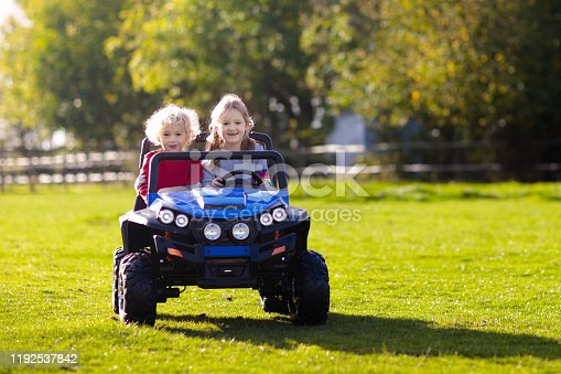 915609494 istock photo Kids driving electric toy car. Outdoor toys. 1192537842