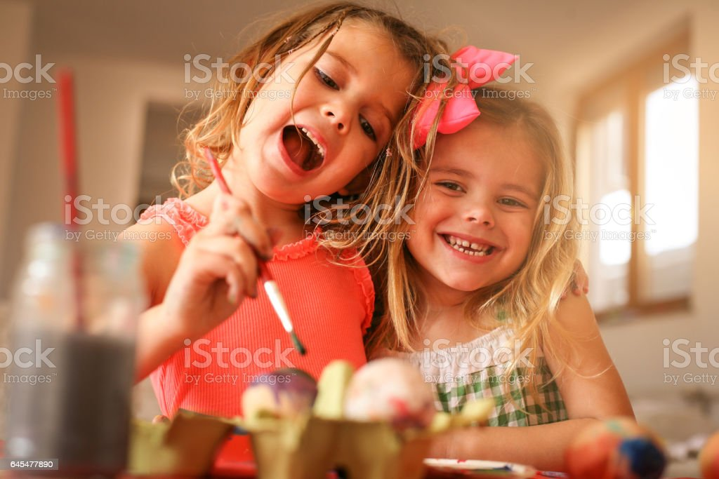 Kids Easter preparation by painting Easter eggs. stock photo