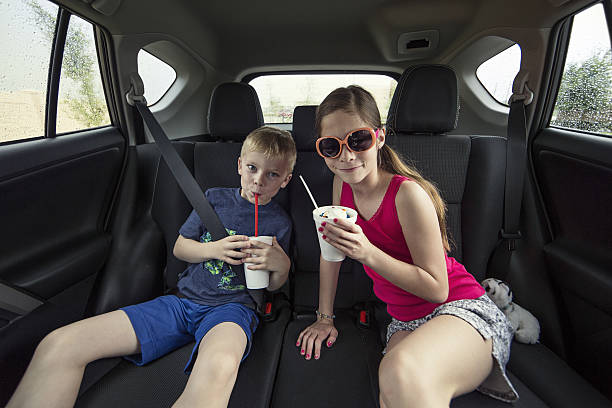 Kids eating a treat in the back of their car stock photo