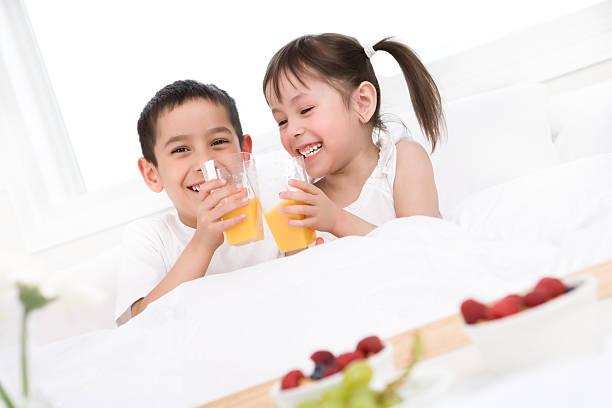 kinder essen ihr frühstück im bett - innocent saft stock-fotos und bilder