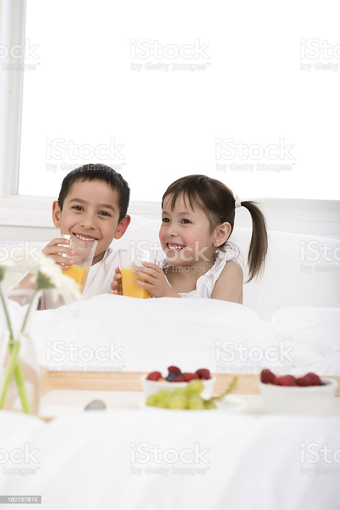 Kids eating breakfast in bed royalty-free stock photo