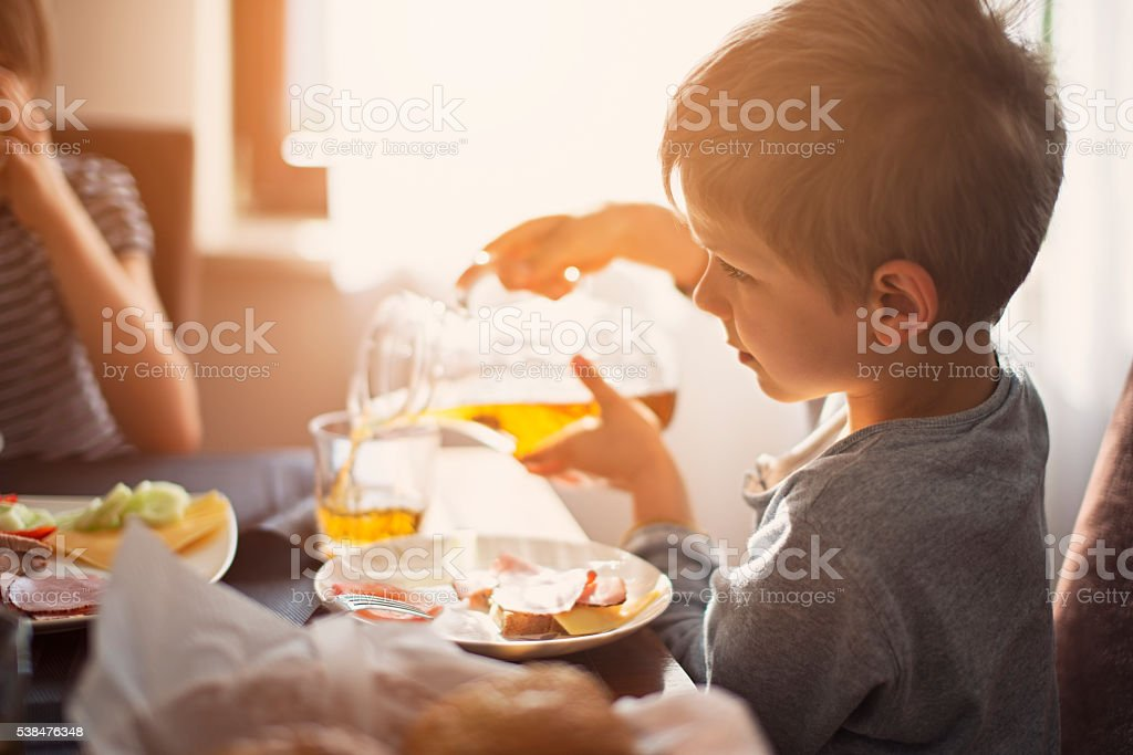 Kids eating breakfast on sunny morning stock photo