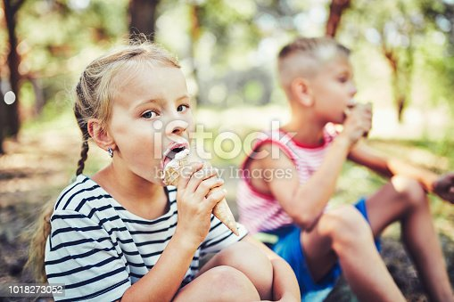 istock Kids eating ice cream on hot summer day on tropical vacation. 1018273052