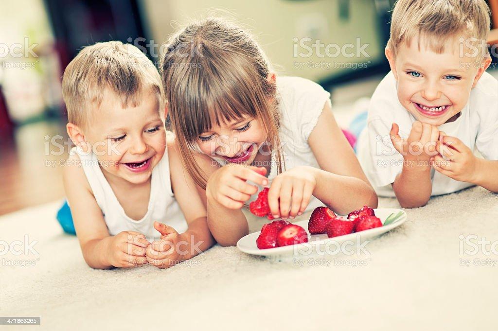 Kids eating strawberries on carpet royalty-free stock photo