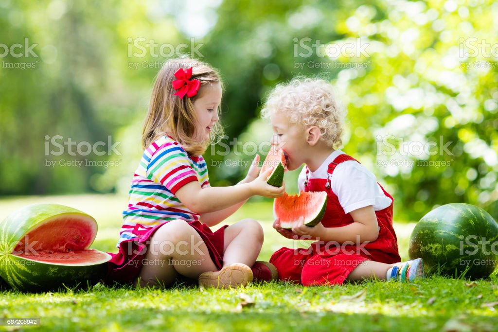Kids eating watermelon in the garden royalty-free stock photo