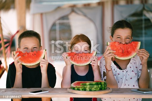 Three kids at the seaside eating sliced watermelon