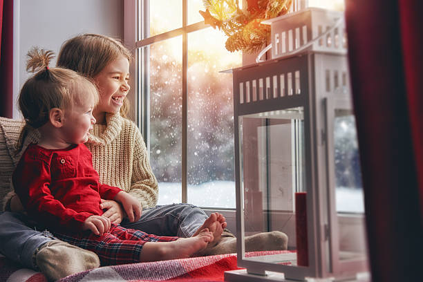 kids enjoy the snowfall - warm house stock photos and pictures