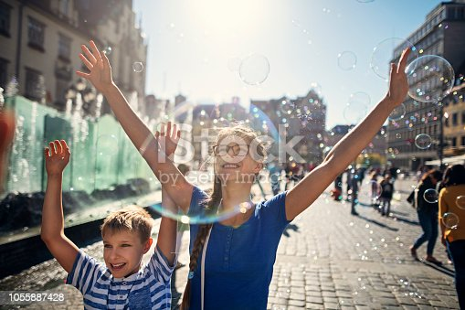 Two kids enjoying bubbles in the air while sightseeing Wrocław, Poland.  Nikon D850