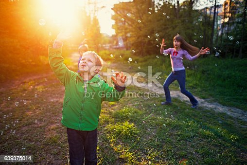 618034312 istock photo Kids enjoying bubbles on spring evening 639375014