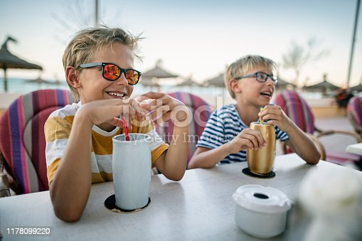 Two boys are drinking juice in beach seafront restaurant.  Nikon D850