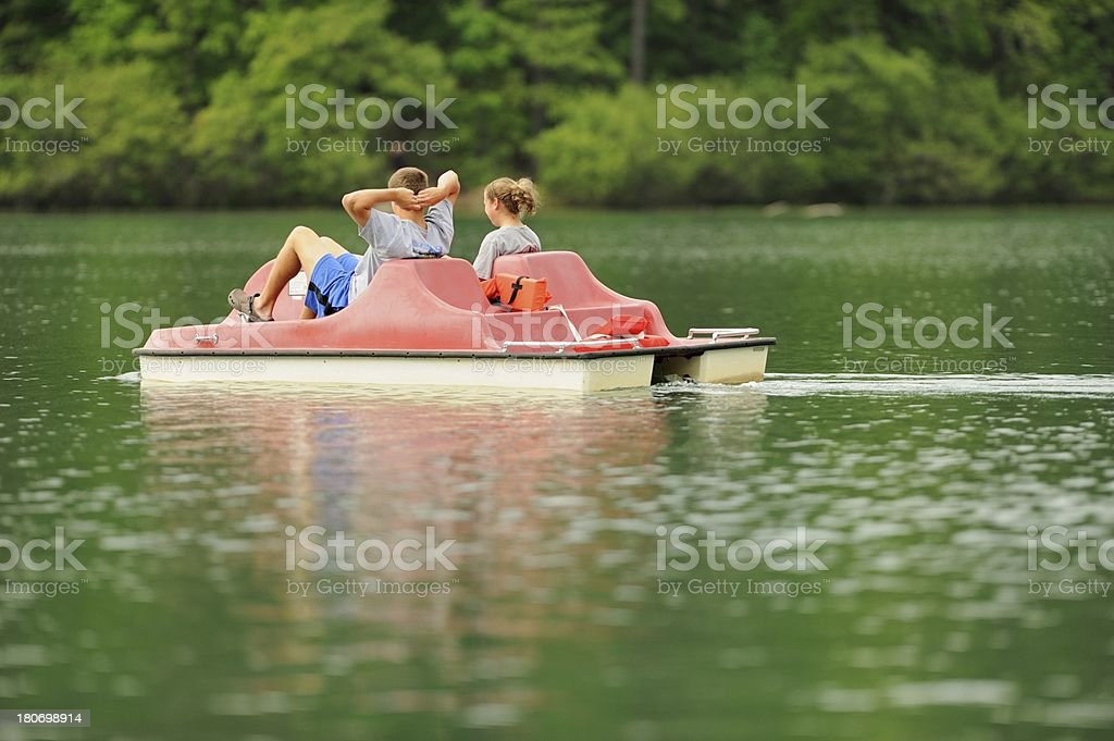 Kids enjoying pedal boat on calm lake royalty-free stock photo