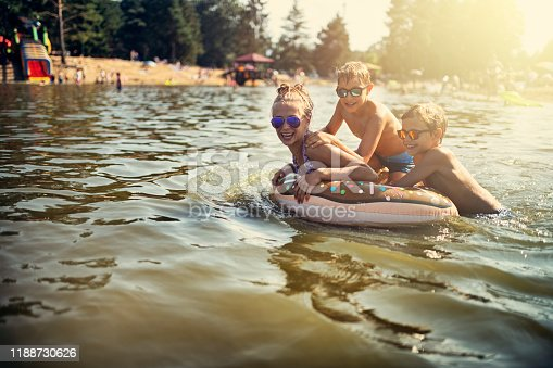 Kids are splashing and having fun on swim ring floating on the lake. Kids are laughing and having fun. Nikon D810