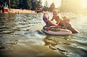 Kids are splashing and having fun on swim ring floating on the lake. Kids are laughing and having fun.\nNikon D810