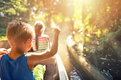 Little boy aged 6 and his elder sister aged 9 are sitting in a small boat, taking a boad ride in on a river flowing in forest.They are enjoying beautiful nature and the sun shining through the forest leaves.