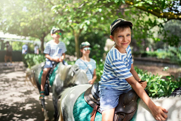 Kids enjoying riding ponies. Kids enjoying pony ride. Little boy is smiling and petting the pony. Sunny summer day. Nikon D850 pony stock pictures, royalty-free photos & images