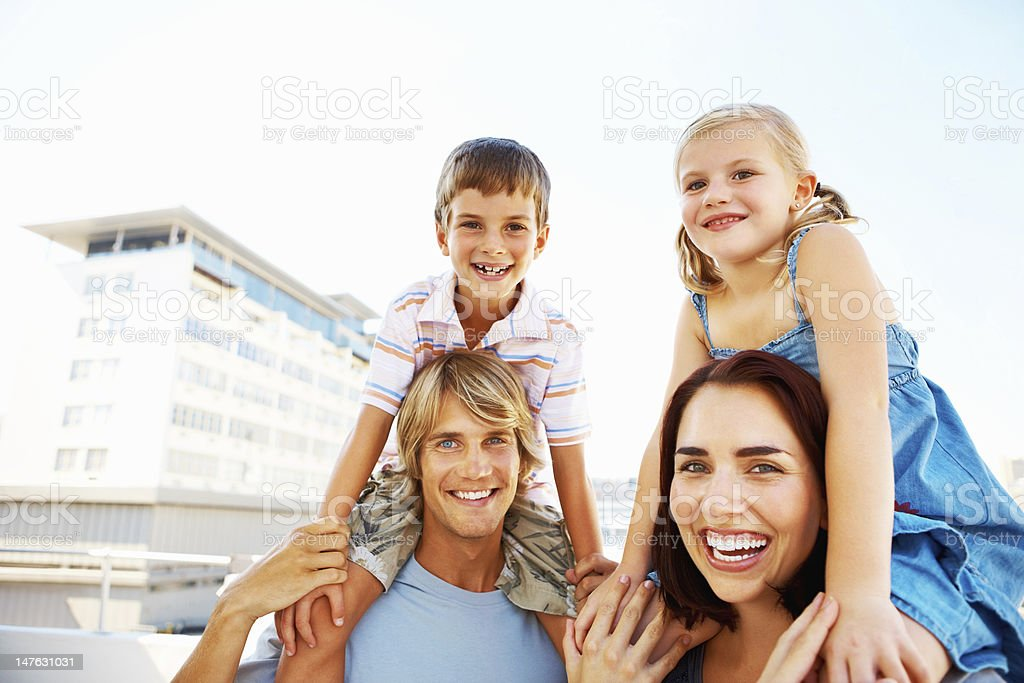 Kids enjoying shoulder rides on young parents royalty-free stock photo
