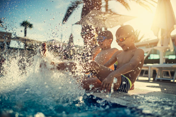 dzieci bawiące się pluskają się w basenie - kurort turystyczny zdjęcia i obrazy z banku zdjęć