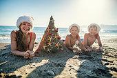 Three kids are having fun during summer Christmas. Family wearing Santa hats is decorating a sand Christmas tree.\nNikon D850
