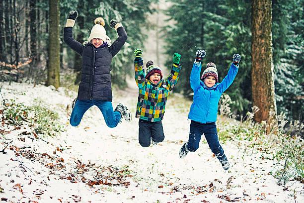 kids enjoying the first snow in winter forest - schneespiele stock-fotos und bilder