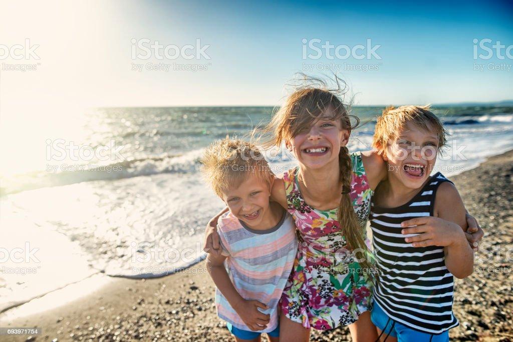 Kids enjoying tuscan beach stock photo
